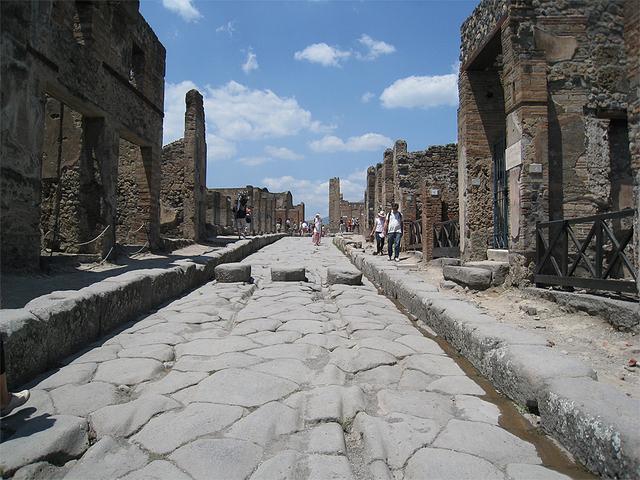 石畳で舗装された道路 中央の車輪跡が残る車道と両脇の歩道がある。